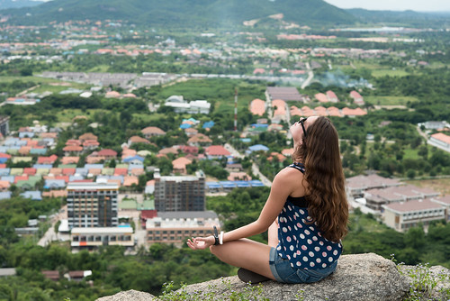 Young woman meditate on the top of mountain background with Hua Hin city.