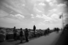 Lone Figure (Sean Anderson Media) Tags: blackandwhite holgalens moddedlens holgaf8mod fisheyeadapter holgafisheyeadapter kenosha kenoshaharbor sonya7rii monochrome streetphotography distorted lonely lonefigure blur clouds rocks lakefront harbor wisconsin