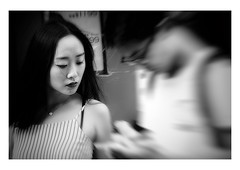 a model of composure (handheld-films) Tags: hongkong candid street portrait portraiture girl couple closeup people stillness calm serenity crowds individual individualism cities citylife asia fareast travel mono blackandwhite chinese model
