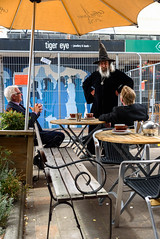 Just Two Left (Jocey K) Tags: newzealand christchurch buildings city signs architecture people street newregentst cafes chairs tables clouds shops mural streetart painting artwork hats wizard bench plants