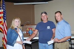 Wayne KY Caudill, center, giving checks to Brittany and Major Crawford