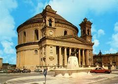 Malta - Mosta [002] - 1979 - front (Ye-Di) Tags: ford church vw postcard beetle kirche malta victor minx mercedesbenz 70s 24 1979 opel vauxhall kfer anglia panhard mosta kapitn hillmann 105e ansichtskarte strichacht w114115 wannabethere r2u kartolina