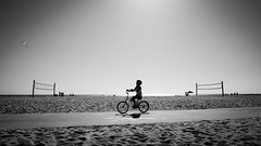 A boy cycling in Venice Beach - Los Angeles, United States - Black and white street photography (Giuseppe Milo (www.pixael.com)) Tags: sand calm peaceful street water city sea summer contrast ocean monochrome photography black wallart white fineart tranquil prints sunset outside bicycle unitedstates faceless streetphotography urban boy venicebeach usa sun photo photograph bw candid cute depth outdoors beach blackandwhite sky losangeles horizontal print onsale