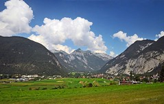 Home is a valley (Vee living life to the full) Tags: italy leger travel touring holiday nikond300 heathaze view road sky cloud blue water light evening sunset sunrays sunburst lowlight highlight people travelling sun mountain landscape rock towers austria