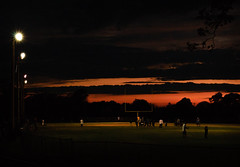 twilight game (andymudrak) Tags: sunset sky game field grass clouds person football twilight branch play crowd lamps treeline plantlife