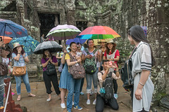 Tourists at Bayon Temple (tmeallen) Tags: laughing cambodia siemreap umbrellas unescoworldheritage ankorwat takingphotos bayontemple backstotemple lilghtrain