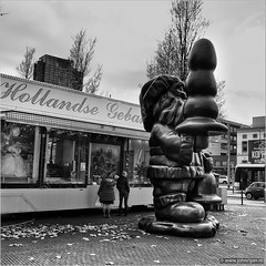 Santa and a X'mas tree (with some fantasy...) (John Riper) Tags: johnriper street photography straatfotografie square vierkant bw black white zwartwit mono monochrome netherlands candid john riper xt1 fuji 18135 artist gnome santa statue eendrachtsplein binnenweg gebakskraam stall oliebollen people fallen falling leaves autumn fall