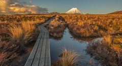 The road to doom (zebedee1971) Tags: landscape track doom mount tongariro national park sunset dusk tussock mountain volcano snow ice winter water reflection pool shallow puddle boardwalk wooden cloud sky orange sun sunlight calm
