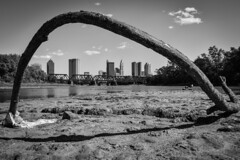 "Skyline Under the ""Arch"" (tim.perdue) Tags: skyline under arch downtown columbus ohio urban city railroad bridge buildings river scioto olentangy confluence park branch dead mud dirt dry riverbed sky clouds black white bw monochrome curved decay trestle sunlight shadow"