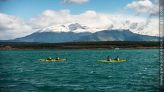 team kayaking with mountain in background