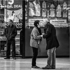 Almost there (John Riper) Tags: johnriper street photography straatfotografie square bw black white zwartwit mono monochrome candid john riper canon 6d 24105 l liverpool england uk people limestreet limestreetstation couple man woman kiss kissing almost nearly mealdeal telegraph shop window goodbye greet evian buxton smartwater water zwvk