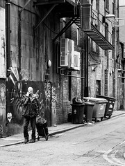 Northern Quarter #138 (Peter.Bartlett) Tags: manchester niksilverefex unitedkingdom facade people urbanarte city olympuspenf streetphotography drainpipe noiretblanc cellphone graffiti lunaphoto man urban peterbartlett candid uk m43 microfourthirds mobilephone bw monochrome wall blackandwhite bin door