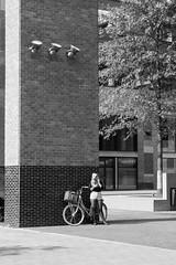 Wachten in de zon (Hans Westerink) Tags: breda noordbrabant nederland nl girl bike fiets meisje sigaret wachten hanswesterink canon 500d eos bicycle beautiful hotpants paysbas architectuur zwartwit monochrome