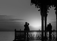 Precious Moments (Fourteenfoottiger) Tags: snapper sunshine backlit happy love silhouettes people photographers candid sunset bandstand ornate architecture victorian railings sea seaside beach coast watching kissing embrace embracing sundown outdoors evening patterns highcontrast structure view landscape seascape