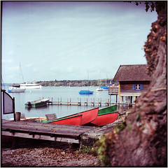 drei rote Boote (Ulla M.) Tags: ammersee bayern expiredfilm greatwall canoscan8800f tetenalcolortec selfdeveloped selbstentwickelt see 6x6 mittelformat boote vignette umphotoart
