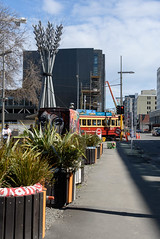 Missed the Tram (Jocey K) Tags: newzealand christchurch sky people plants streetart clouds buildings spring artwork mural shadows tram cranes seats cbd flax sculputre archtiecture rebuilds gapfiller herefordst greeningtherubble