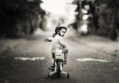 Cycling through the park (Wojtek Piatek) Tags: road park portrait blackandwhite bike bicycle vintage fun mono cycling back kid child looking sony helmet cycle rower stabilizer a99 zeiss135