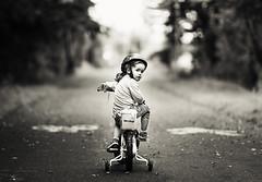 Cycling through the park (Wojtek Piatek) Tags: road park portrait blackandwhite bike bicycle vintage fun mono cycling back kid child looking sony helmet cycle rower stabilizer a99 zeiss135