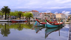 The colourful Moliceiros at the serene waters of Aveiro (B℮n) Tags: portugal aveiro moliceiros boat gondel traditionally charm magic hidden gem reflections water canals maritime colour fishermen paintwork azulejo fishing veice lagoon urban festival seaweed tourist holiday vacation pink yellow colors blue round city hopping ornate images man woman clouds weather after rain gondelas serene 100faves topf100