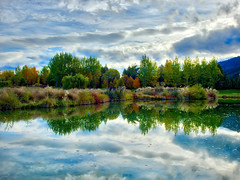 More Color Change In Arrowtown (Stuck in Customs) Tags: autumn newzealand trey ratcliff stuckincustoms stuckincustomscom treyratcliff rr dailyphoto horizontal colour color art sculpture thehills golfcourse bridge pond sunset man reflection water sky cloud green grass blue white tussock trees willow mountain rock stone glare sun orange yellow brown fawn grey black dusk red metal standing queenstown otago southisland michaelhill arrowtown outdoor serene hasselblad h5d april 2016 p2016 bright landscape plant foliage hcd 3590