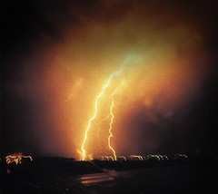 In the car,  slowing down w/ one hand on the camera.  First picture of lightning I ever took.   Stormchasing in Kansas. (Jaye Eryk) Tags: lightning strike amber yellow orange storm stormchasing kansas