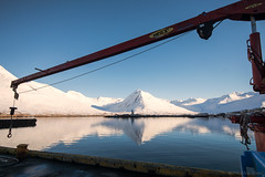 Nearby some unfamiliar settlement (OR_U) Tags: 2016 oru iceland fjord sea reflection crane blue red sky water mountains snow ice village coast harbour framed heila machinery siglufjrur