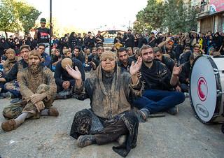 iranian shiite muslim woman covered in mud praying in the middle of men during ashura day, Kurdistan Province, Bijar, Iran