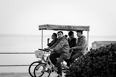 The patrol (Go-tea ) Tags: canon eos 100d asia street urban city qingdao huangdao china asian chinese people outside outdoor monochrome bw bnw black white blackwhite blackandwhithe men young team group friends fun time enjoying riding ride bicycle roof tree sea side shore lines movement effort spoted patrol squad crew friendship coast coat glasses candide 4 together sport