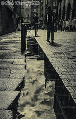 Shower Avoiding City Dwellers (Nick Biswell) Tags: bccpoty2016round8rain unitedkingdom london sony a100 chinatown street rain shower puddle reflection tamron monochrome blackandwhite niksoftware silverefexpro wide wideangle cloud clouds man woman lady bollard pavement paving long crowd people wet