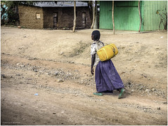 Carrying water home. 20+ kg? (Luc V. de Zeeuw) Tags: 20 20kg carrying dirtroad ethiopia girl house hut jerrycane water yellow kg konso southernnationsnationalitiesandpeoplesregion