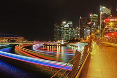 Light trails (elenaleong) Tags: bridge skyline boats singapore nightscape jubilee citylights esplanade merlion jubileebridge marinabay marinareservoir mbslasershow livecomposite