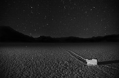 Racing across the playa at night (PeterThoeny) Tags: deathvally night sky nightsky desert racetrackplaya sailingstones movingstones movingrocks move track lakebed playa california hdr 1xp raw nex6 selp1650 photomatix outdoor qualityhdr qualityhdrphotography landscape slidingrocks rollingstones blackandwhite monochrome minimalism texture fav200 drylakebed