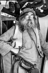 Shopkeeper - Medieval Market (Sebastian Schmidt) Tags: portrait people blackandwhite man hat shirt beard glasses mirror blackwhite belt shoes market outdoor medieval pouch vest satchel shopkeeper medievalmarket sebastianschmidt