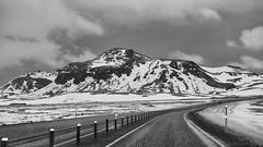 on the road to the South (Iceland) (lunaryuna) Tags: iceland road reykjaviktoselfoss journeysouth ontheroad curve mountains winter snow ice landscape travel journey voyage roadtrip blackwhite bw monochrome lunaryuna